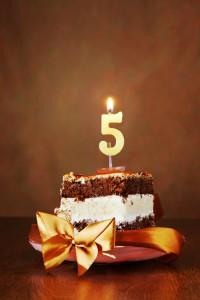 Piece of Birthday Chocolate Cake with Burning Candle as a Number Five on Brown Background
